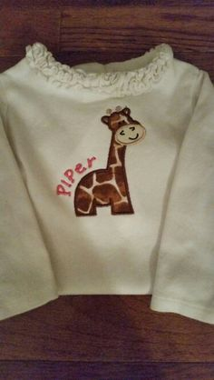 Giraffe applique from The Itch 2 Stitch. Used 4x4 size on a 3-6 mo onesie. The applique pattern is for solid fabric for giraffe body and embroidered brown spots. I deleted the step to do the spots (#7) and just used giraffe pattern fabric instead.. Font is Jumping Bean. I did the name as a circle on Embrilliance and adjusted to try to get the right curve. Floated on cutaway. Top of giraffe horns 2 fingers down from neckline.