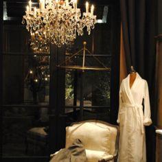 Restoration Hardware - love the dark wood of this window frame next to the sparkly, opulent chandelier, cozy chair & bath robe