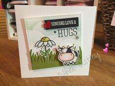 "I created a simple scene using a cloud die as a stencil and a grass border die from Lawn Fawn. The sentiment is from Simon Says Stamp ""best hugs"" set and the daisy is from Paper Smooches Gleeful Gardens. Finally, the cow is from Mama Elephants Lunar Animals and coloured using Copics"