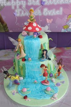 TinkerBell Cake - I made this TinkerBell cake for my daughter's 3rd birthday. The top tier is Pam's Chocolate Cake with Nutella filling and choc ganache. The bottom tier is orange-almond cake with white choc ganache. The big toadstool is fondant and the characters are all figurines that I purchased.