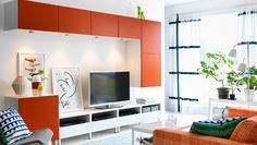 Unidad de almacenaje para TV blanca y naranja en salón moderno
