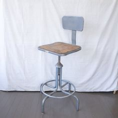 "Vintage, industrial drafting stool with great machine age design. It has seen years of use in a factory and is now ready to come to your home!This wonderful retro shop stool is made of industrial gray metal with a brown seat and a metal back rest. The height of the chair is fully adjustable. There is normal wear and scrapes on the metal legs and seat back. There are some imperfections in the seat as shown in the photos. The stool has been left in its ""as found"" condition with its natural… Vintage Industrial, Industrial House, Machine Age, Stool, Chair, Light Fixture Covers, Im Not Perfect, Stage Props, Rest"