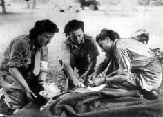 Nurses (Anne-Marie Branet, right, and Michette De Valence, left) of the French 2nd Armored Division 'Les Rochambelles' working on a patient ~