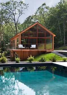 Casa de campo de madeira com grandes painéis de vidro e ampla sacada.