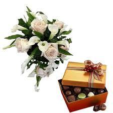Bouquet di rose e calle bianche accompagnati da una scatola di cioccolatini