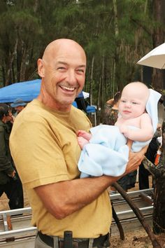 behind the scenes On Lost. Locke holding the baby that was born on the island- the baby is adorable!