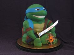 Leonardo - Teenage Mutant Ninja Turtle - Cake is carved  from chocolate mud cake (shell and torso), chocolate buttercake (legs) and my own chocolate rice krispy recipe (head and arms). Entire shape covered in chocolate ganache underneath coloured fondant. Bandana over shoulder strengthened with cellogen (gel)  powder. The non-edible parts (katana, holster (on back) and shuriken) are plastic from a non-TMNT Ninja kids play set (if you can believe that!). Loads of fun to make, and a welcome…