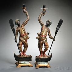 Pair of Italian Baroque-style Carved, Painted, and Gilded Wood Blackamoor Candlesticks, Venice, late 19th/early 20th century, each figure raising a sconce above his head with one arm while holding an oar in the other, and standing atop a gondola stern.