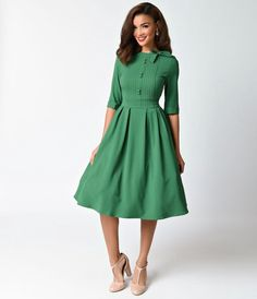 Flocked in green! A prim and precise vintage inspired frock, The Madison Dress from Hell Bunny is a captivating number with meticulous bodice details. Cast in a lush green and featuring a pleated seamed top with a faux button up style and a wrap around co