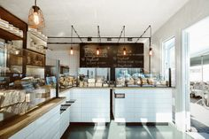 Wire-encased lights are suspended above oak-topped counters at this bakery in Poland by designer Maciej Kurkowski.