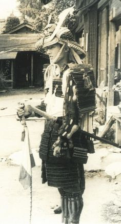 Samurai wearing full armor and holding a muchi (whip).