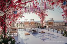 Beachside mandap in white, red, and pink floral decor at Goa