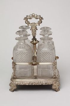 "*1820-1830 British Spirit stand at the Victoria and Albert Museum, London - From the curators' comments: ""The spirit stand or decanter frame was a receptacle which could support from two to six decanters. Such pieces were made in a variety of styles but this particular example has a square base with rounded angles, sits on four rococo feet, and the bottles are held in openwork compartments with central handle."""