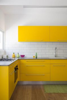 Yellow Kitchen Decor to Brighten Your Cooking Space - DIY Home Art - a modern yellow kitchen with stainless steel countertops and a white tile backsplash looks very eye - Yellow Kitchen Cabinets, Yellow Kitchen Decor, Kitchen Tiles, Kitchen Countertops, Diy Kitchen, Kitchen Design, Kitchen Modern, White Cabinets, Kitchen Upstairs
