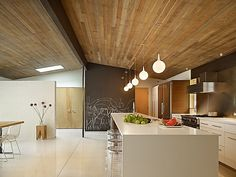 I want this in my dream home TileFlooring WoodCeiling StainlessSteel PendantLight BreakfastBar Refrigerator HalfWall Hood Kitchen