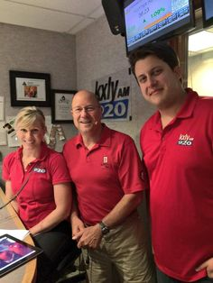 """The morning crew, Kristi, Bud, and new overnight editor Shawn Goggins, showing the colors for """"Wear Red Friday""""."""