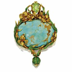 Gold, turquoise, peridot and enamel pendant brooch, Marcus & Co. circa 1900. The oval cabochon turquoise measuring approximately 40.0 by 28.0 by 11.0 mm., within a gold frame of iris and leaves set with a pear-shaped peridot, applied with green and brick-colored enamel, suspending a pendant applied with green enamel, signed M & Co. for Marcus & Co.