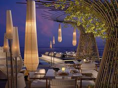 Outdoor dining area at The Romanos, Costa Navarino, Greece - mkv design. Paper lanterns and floor lamps
