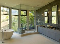 This expansive glass-enclosed shower, complete with views of the Hollywood Hills, boasts a lovely dark-gray Jerusalem stone wall — and a boulder-like lava rock shower bench. The floor is limestone with minimal joint grouting, which makes the modern freestanding tub seem to float in the airy space.