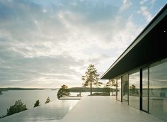 On the side facing the lake, the stone slabs expand to a spacious terrace with sunken swimming pool.