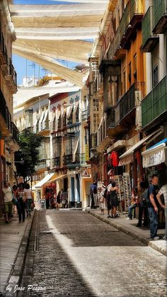 Sevilla is crazy hot in summer. They hang white sheets across the streets and alleys to give shade and cut the heat.
