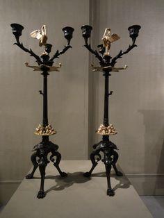 """""""Paire De Chandeliers En Bronze Patiné et Doré"""" Paire de chandeliers tripodes aux hérons et aux masques de tragédieà 3 bras de lumière en bronze patiné et doré. Travail dans le goût néo-pompéien. Epoque Napoléon III."""