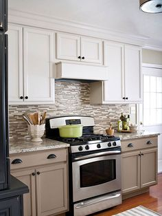 Create Drama with Contrasts Take painting cabinets to the next level by using contrasting colors. Here, a creamy taupe on the lower cabinets grounds the kitchen, while a lighter, warm white on the uppers keeps the look airy.