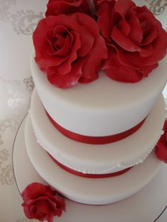 "Red Rose Wedding Cake - 10"", 8"", 6"" wedding cake, covered with white fondant and decorated with hand made red roses, dusted with silver lustre dust and silver bear grass (which doesn't show up on the main photo but does on the extra photo)"