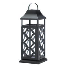 """This black iron candle lantern is just what you need to amplify the style in your living space. The iron frame feature a beautiful geometric damask design and a hanging loop at top. It's ready to glow when you place the candle of your choice inside. Item weight: 4.4 lbs. 7¼"""" x 7¼"""" x 20"""" high. Iron and glass. Candle not included. UPC: 849179026301."""