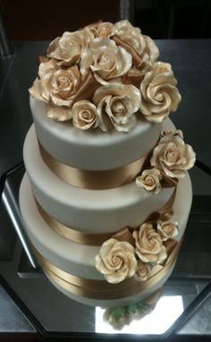 Silver cake with gold roses and ribbons