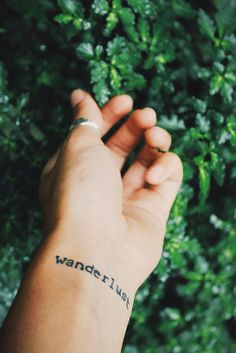 wanderlust tattoo on the back of my bicep