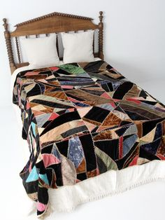 """Circa 1910s An antique mixed textile """"crazy"""" quilt. This style of quilt became in fashion during the late Victorian. The hand-stitched quilt features a variety of textiles, primarily in velvet and woo"""