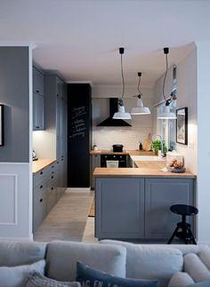 Półotwarta na salon kuchnia bazuje na zabudowie o barwie szarego błękitu…