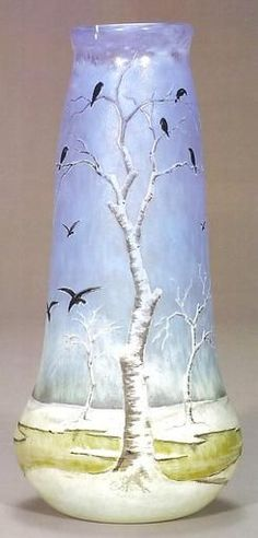 """A supreme Daum Nancy cameo vase featuring a landscape shrouded in snow. A yellow river meanders through the isolated setting as a flock of sixteen black birds are in flight or have just perched in barren birch trees, gathering for the evening roost. This tranquil setting is silhouetted against a beautiful mottled sky of blue. Enamel signed """"Daum Nancy"""" with the croix of Lorraine."""