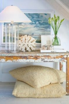 Coastal farmhouse decor featuring a rustic wood side table, seascape painting, coral, jars of shells in a tray and a clear glass lamp - Coastal Beach House Ideas