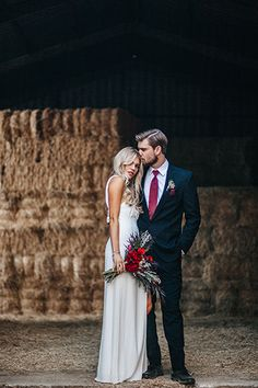 Bohemian barn wedding rustic photo shoot bride long white gown with long slit by leg and groom black suit with white dress shirt and burgundy long tie with matching burgundy pocket square standing by haystacks