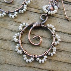 Bead Dance is one of my favorite earring designs. These dangle wire wrapped hoops have seed beaded petals of gorgeous pearly white glass seed beads. The pearly white color of the beads contrasts nicely with the antiqued copper and gives the appearance of white lace edges. The