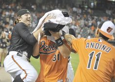 Taylor Teagarden has shaving cream shoved in his face by teammates Mark Reynolds (left) and Robert Andino.