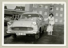 """https://flic.kr/p/kjvz1e   Opel Rekord P1   A brunette lady in a white female suit and her little daughter – also dressed in white – posing with an Opel. A newly built block of flats and a shop named """"Josef Jörres"""" can be seen in the background. The car is registered in the West German district of Düren. Country of origin: Germany"""