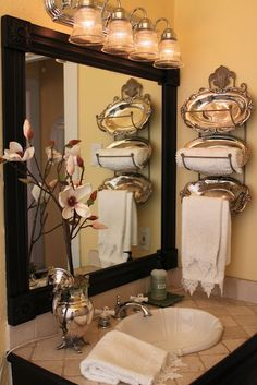 Silver trays in towel rack - framed out builders grade mirror - very sweet for a small guest bathroom