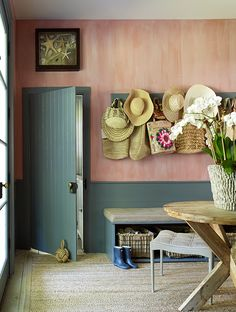 In a sunny mudroom where salty breezes blow through, the coral walls were painted and treated to look faded against the aqua green wainscoting.   Photographer: Tria Giovan