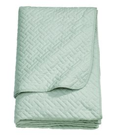 Dusky green. Quilted bedspread in woven cotton fabric with polyester padding.