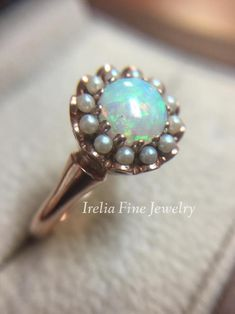 An option for the non traditional bride, this gorgeous vintage inspired 14K Rose Gold Engagement Ring with Opal Center and halo of Seed Pearls.