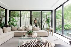 Instead of solid walls, the living area is surrounded with floor-to-ceiling glass. These clear glass panels let the light in and make the space look even bigger than it already is. The room is furnished with an L-shaped sectional sofa, a clear coffee table, and a zebra-print rug.�