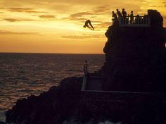 Photo: Cliff divers at dusk. «