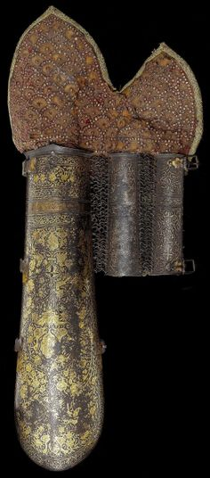 Persian bazu band (vambrace / arm guard), 19th century, shaped to the fore-arm and decorated overall with gold-damascened foliage inhabited by pairs of birds, wrist-plates (one pitted) damascened with gold scrollwork and attached by butted mail, original velvet liner, and earlier Indian hand-defense (worn and damaged) studded with a scaled design of gilt-copper nails, 49 cm.