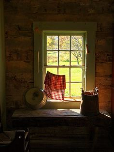 FARMHOUSE – INTERIOR – vintage early american farmhouse showcases raised panel walls, barn wood floor, exposed beamed ceiling, and a simple style for moulding and trim, like in this farmhouse window view.