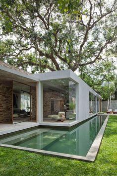 A parte interna da casa se revela já do exterior, a entrada é feita pela porta espelhada pivotante