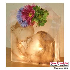 DIY Glass Block Photo Light - Print your photo on self-adhesive transparency sheet (available at any office supplies store). Adhere to front of glass block. Place lights inside the block. Add bow and flowers.  Supplies available at our Ben Franklin Crafts store in Monroe, WA. 360-794-6745