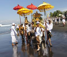 Balinese Hindus carrying Pratima, the symbol of God, walk on a beach during a cleansing ceremony called Melasti in Gianyar, Bali, Indonesia.